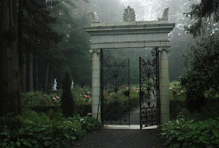 A white marble entry way into the gardens with mist all around.