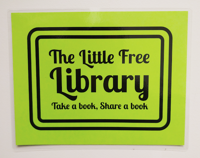 """A green sign with the text """"The Little Free Library: Take a book, Share a book"""""""