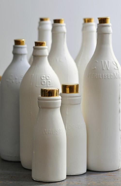 Weiße Flaschen mit goldenen Verschlüssen stehen nebeneinander
