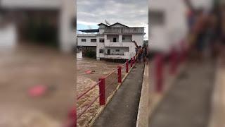 Vídeo mostra jovens desafiando cheia de rio e um deles é levado pela correnteza