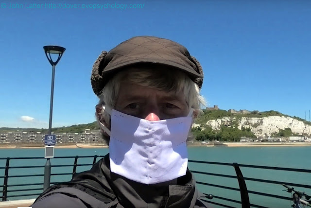 Homemade Personal Protection Equipment (P.P.E.) face mask made with a handkerchief, staples, and two elastic ear loops. The harbour, Dover Castle and iconic White Cliffs are in the background. Photo taken on a cycling ride during the Coronavirus pandemic