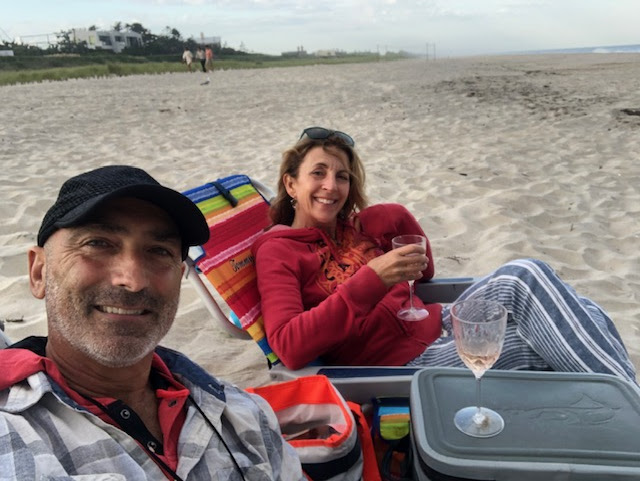 Smiling couple enjoying a picnic on the beach with wine