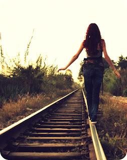 Jovem caminhada por trilho de trem.