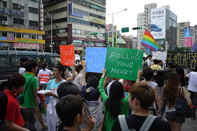 "young women hold signs that say ""Follow Your Heart"" and ""Equal Love"" at 2011 Taiwan LGBT Pride Parade"