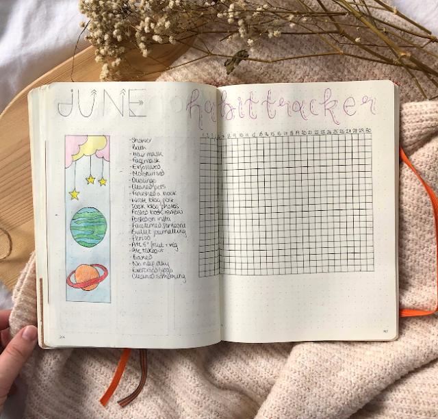 Dotted journal with a habit tracker table in it and a strip of coloured in planets to the left