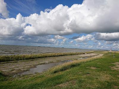 Badestelle Wesselburenerkoog bei Nipptide. Nordsee, Wolken am Himmel, das Wasser reicht zum Deichfuß.