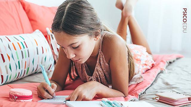 Menina escrevendo em caderno em cima da cama