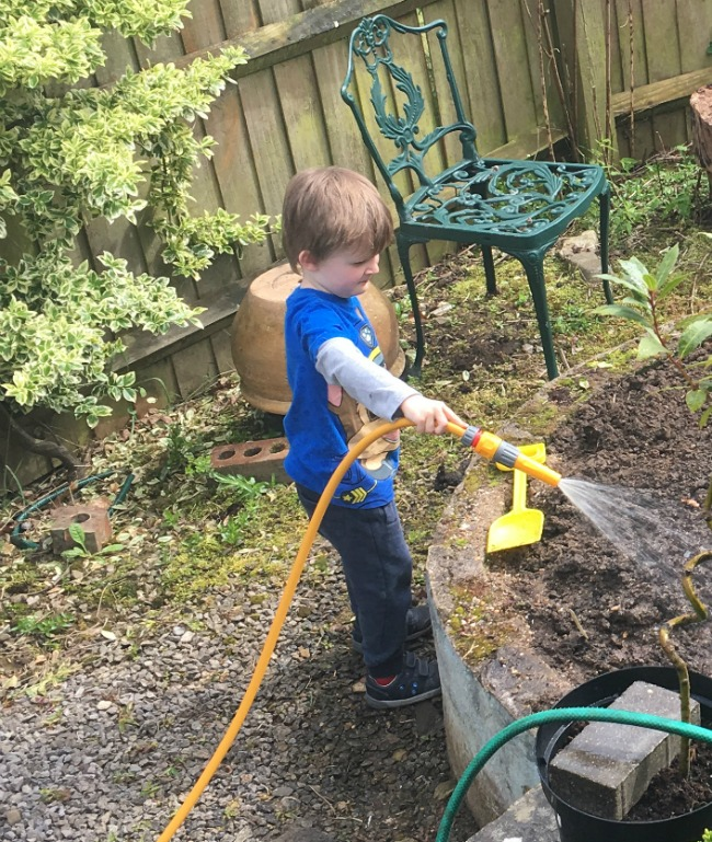 boy-watering-ground-with-newly-planted-potatoes