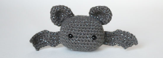 Amigurumi bat made from dark gray yarn with hints of metallic sparkle on a white background.