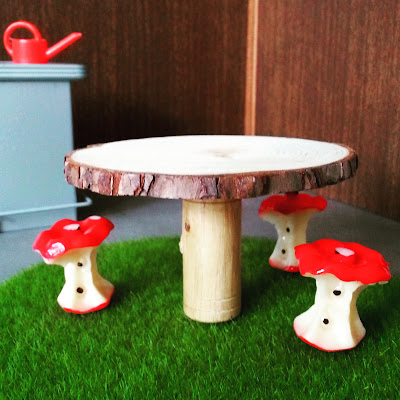 Three 1/12 scale modern miniature stools in the shape of apple cores around a table made with a slice of tree with bark still on it, on a round mat of fake grass. In the background is a bar with a red watering can on it.
