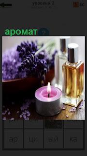 На столе свеча горит, духи, цветы, благовония и аромат
