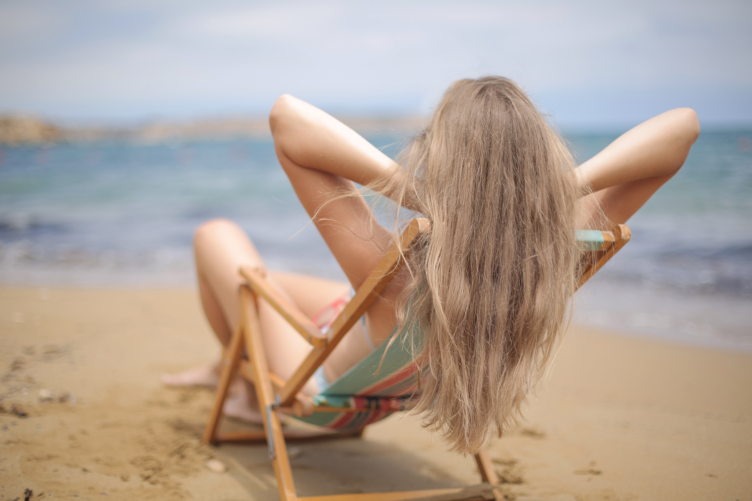 a picture of a woman at the beach touching her hair