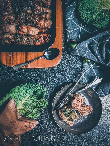 Titelbild: Fertige Kohlrouladen liegen im Bräter. Auf einem Teller ist eine Kohlrouladen angeschnitten serviert