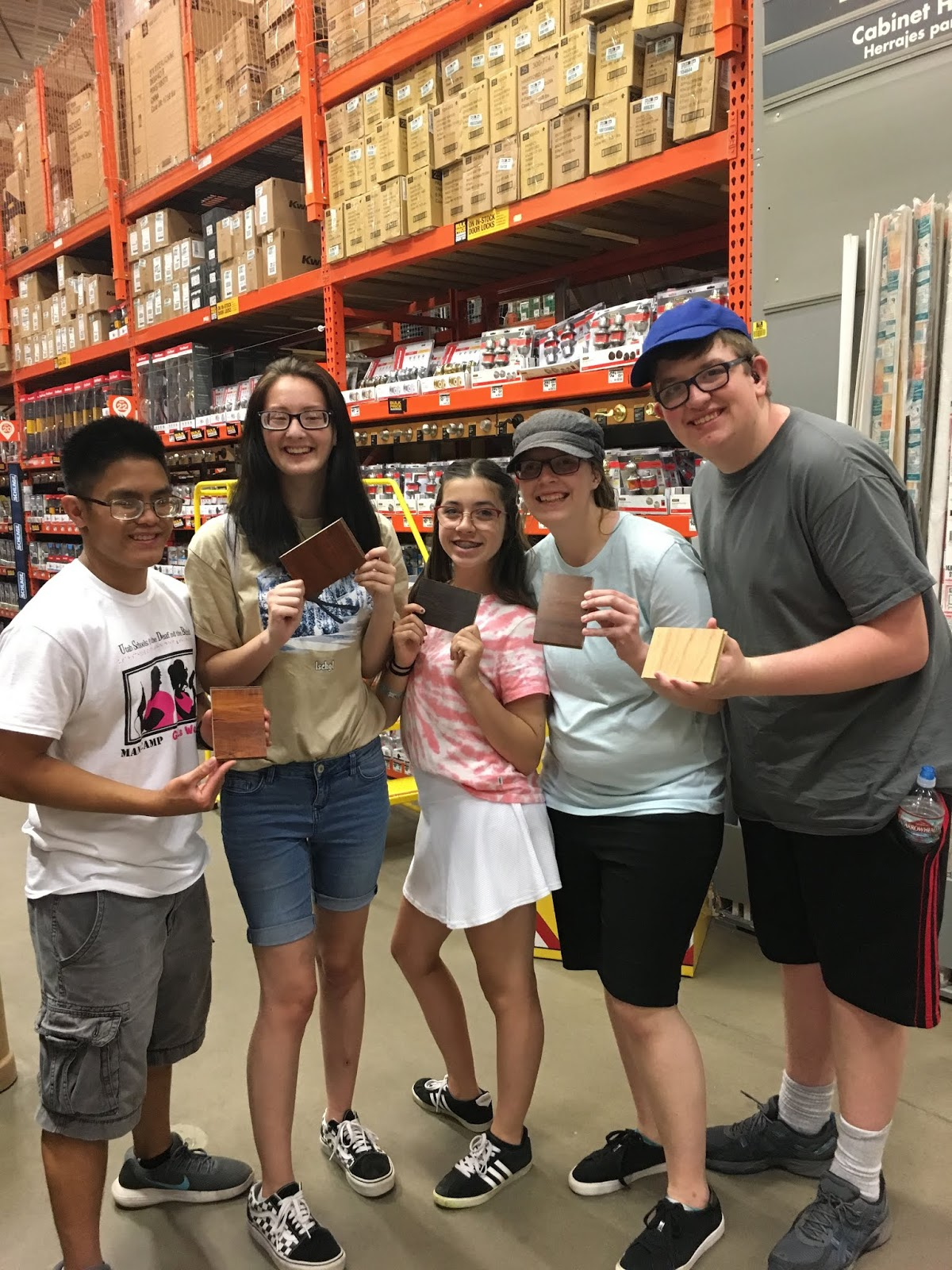 a group of teenagers hold up flooring samples and smile for a picture