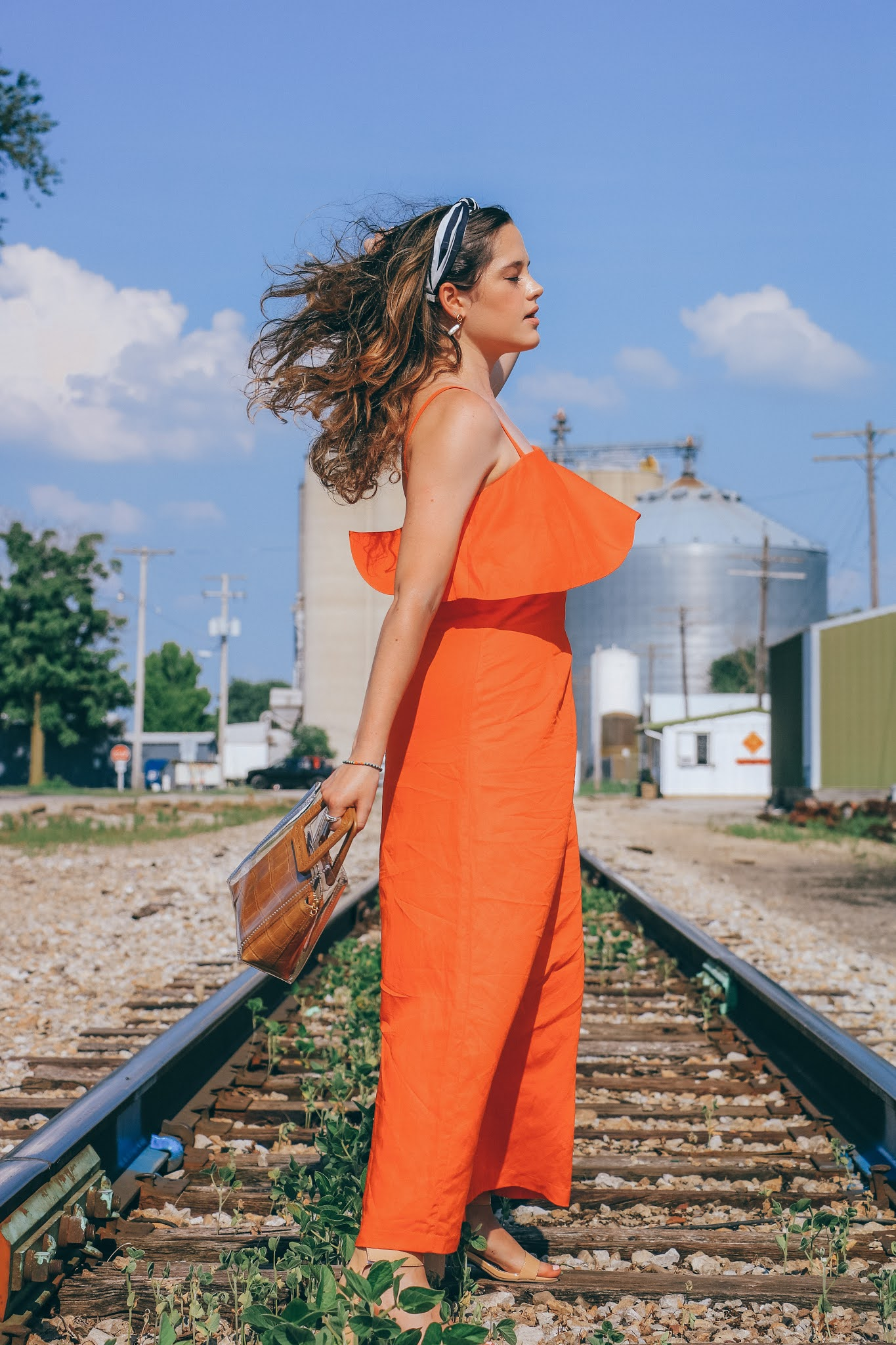 Fashion blogger Kathleen Harper wearing an orange summer maxi dress during an outdoor photo shoot.