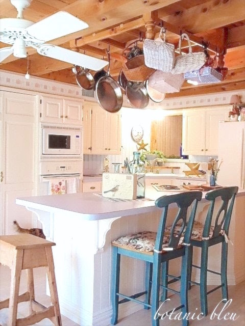 country-french-kitchen-with-wood-beam-ceiling-wood-pot-rack-white-cabinets