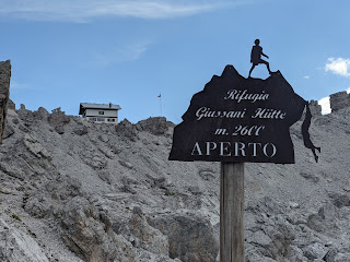 A sign saying that Rifugio Giussani is open, thankfully.