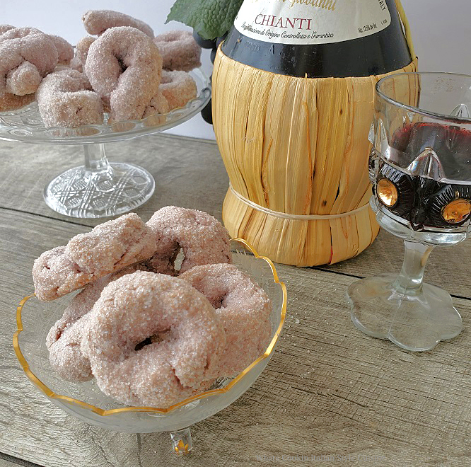sugar coated red wine cookies on a glass pedestal and in a footed gold etched dish