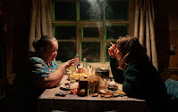 Two women at night talking over a dining table