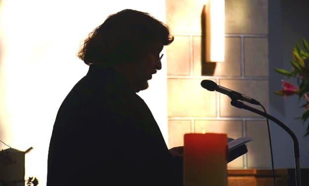 A imagem mostra a sombra de um pastor de perfil segurando uma bíblia com uma luz forte ao fundo.