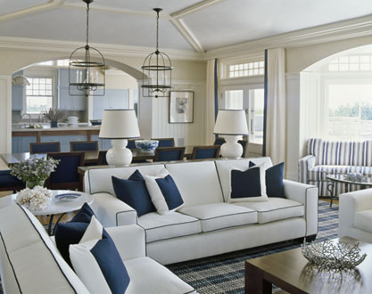 Nautical living room with a blue and white striped sofa, white curtains with a single blue strip where they meet, pendant lights and two white sofas with blue piping