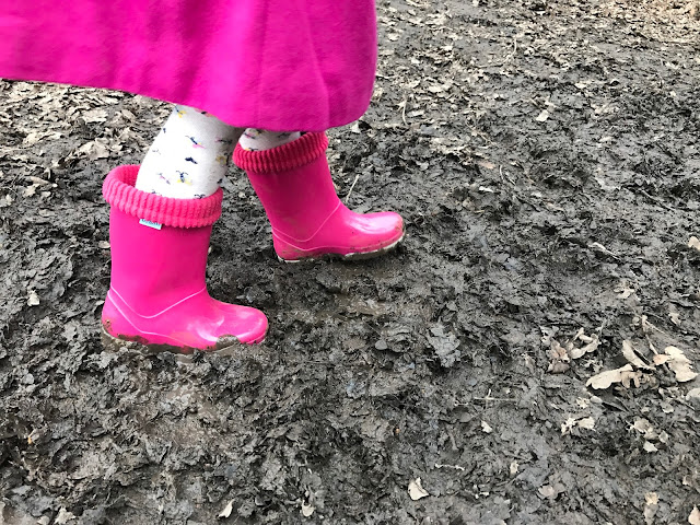 A girl wearing a pair of pink Term wellies and walking in wet mud mixed with dried leaves