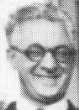 A grinning, middle-aged white man with salt-and-pepper hair and round dark eyeglasses