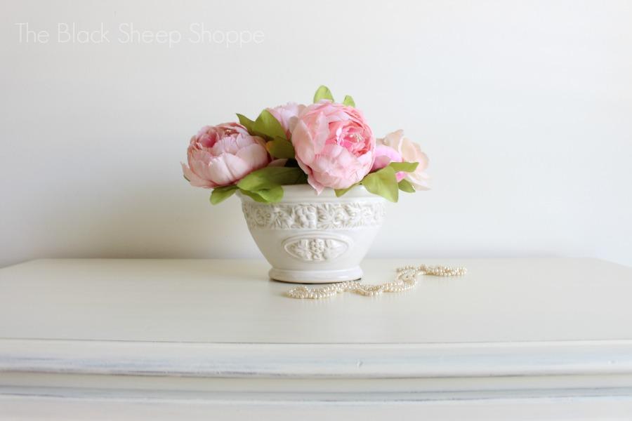 Peonies in vase on top of dresser.