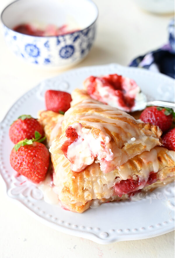 close up of a white plate with cherry turnovers with cream cheese