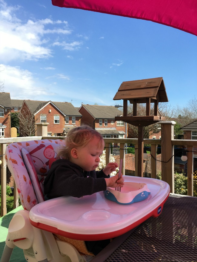 toddler in high chair outside under bright pink umbrella