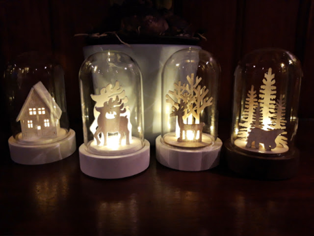 Four Christmas light decorations - one is a house, the next is two reindeer, the third is a reindeer and trees and the fourth is a polar in pine trees