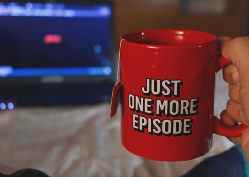 Cup saying 'one more episode' in a post about 10 feel-good TV and films for a self-care night