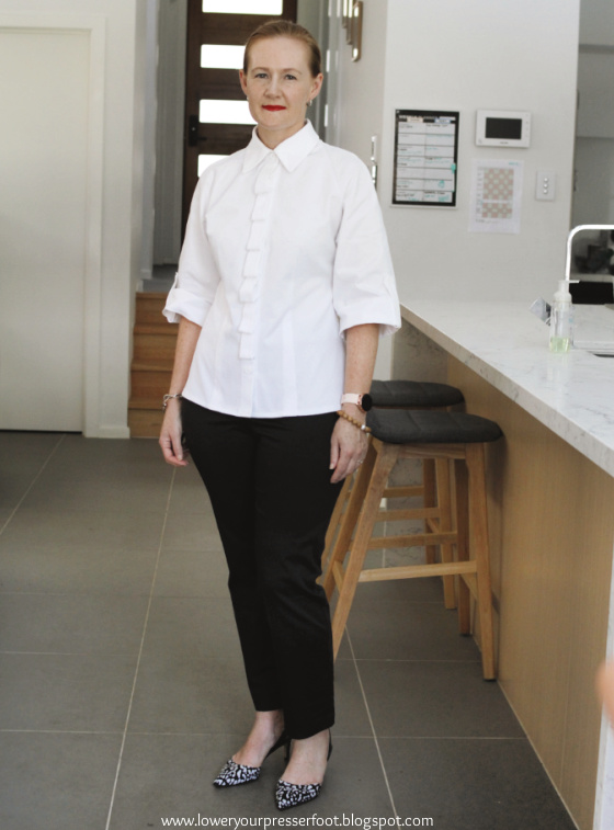 woman posing in a white shirt and black pants