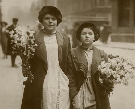 Vintage photo. Two Edwardian era girls stand by the street with flowers. Housekeeping A Word to Women by Mrs. C. E. Humphry, 1898. marchmatron.com