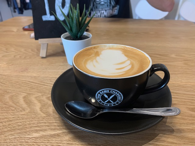 A flat white in a black cup and saucer