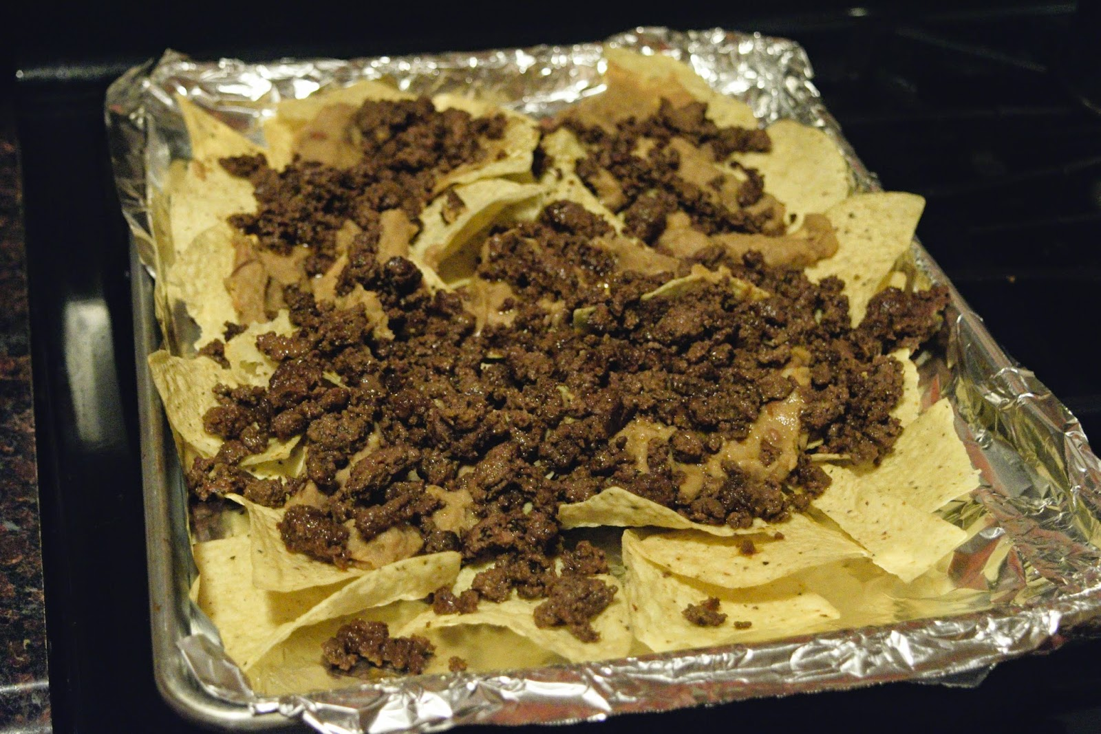 The cooked  ground beef being added to the baking sheet for the nachos supreme recipe.