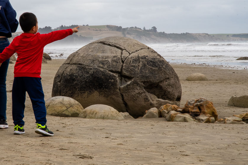A boys points to the sea from beside a Moeraki Boulder.