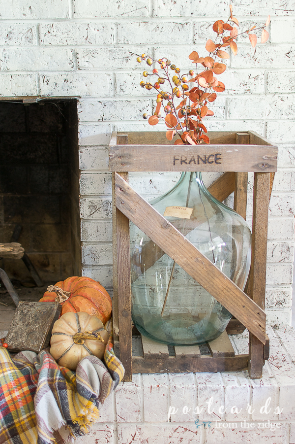 vintage blue demijohn in wood crate with fall decor