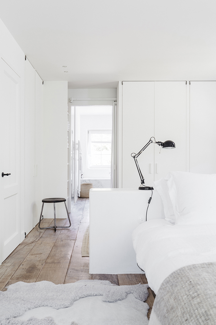 Bedroom with low wall as nightstand and room divider. Summer house in neutral tones design by Peter Ivens and Bea Mombaers