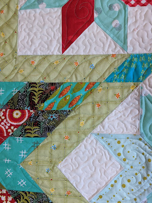 S shapes are free motion quilted along the length of the green border