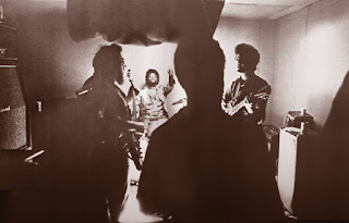 Harvey Brooks, Herbie Rich and Mike Bloomfield rehearse in their Sausalito Heliport practice room as Buddy Miles conducts in the fall of 1967. From The Photography of Rock, Bobbs-Merrill 1972