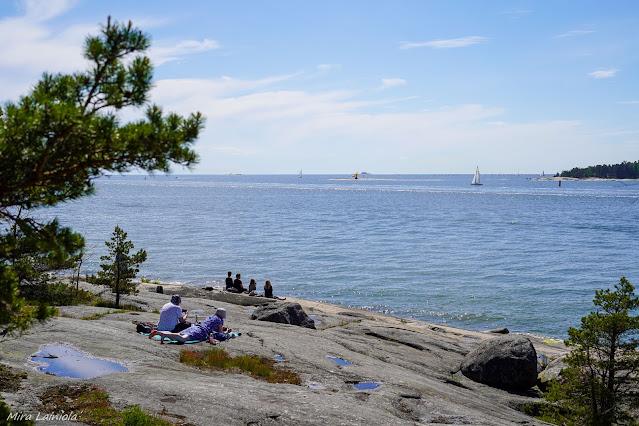 Ihmisiä istumassa rantakallioilla