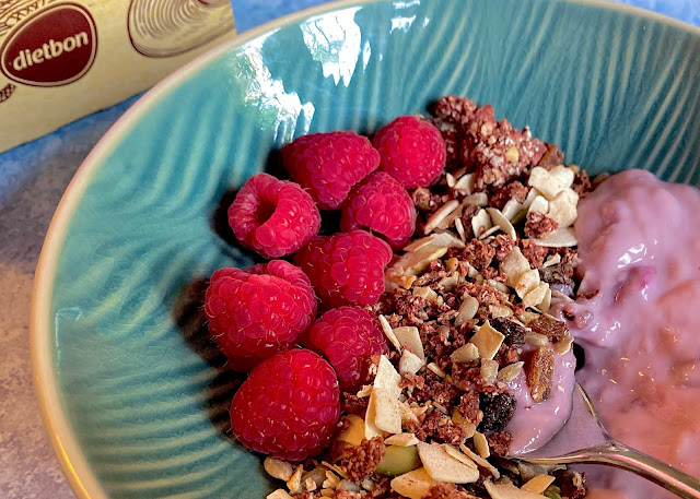 Close up of Dietbon berry granola breakfast with fresh raspberries and dairy free yoghurt