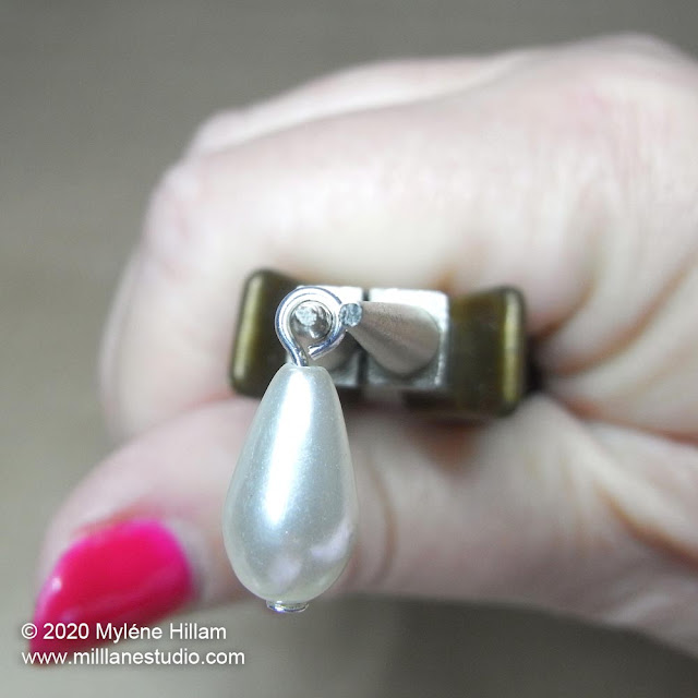 A pearl teardrop strung on a head pin with a simple loop on the jaws of round nose pliers.