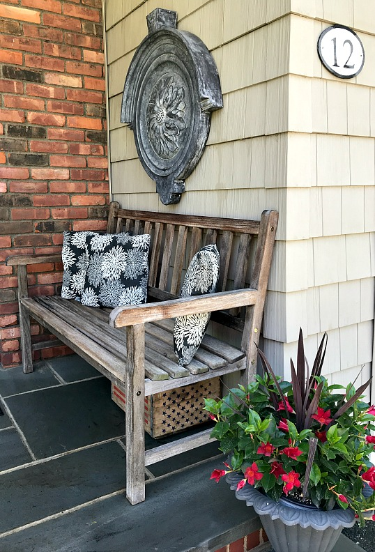 Teak bench at front of house with potted plant in iron planter