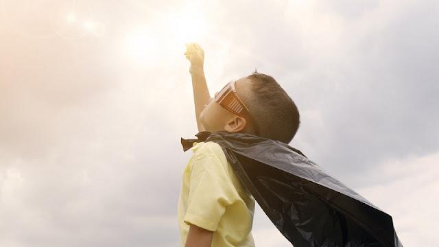 seorang anak yang sedang berpura-pura menjadi superman merupakan simbol optimisme