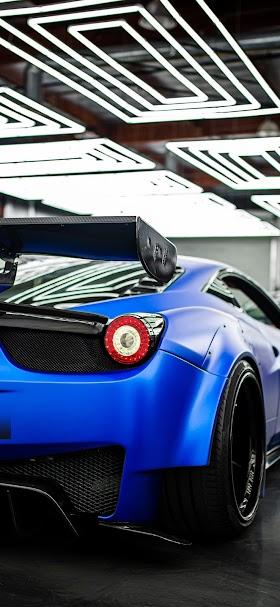 خلفية القسم الخلفي لسيارة فيراري رياضية زرقاء داخل موقف سيارات