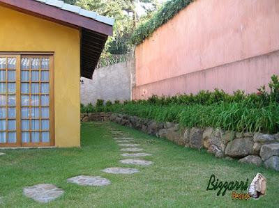 Construção do muro de pedra sem cimento com os caminhos de pedra com pedra bruta e a execução do paisagismo em residência em Mairiporã-SP.