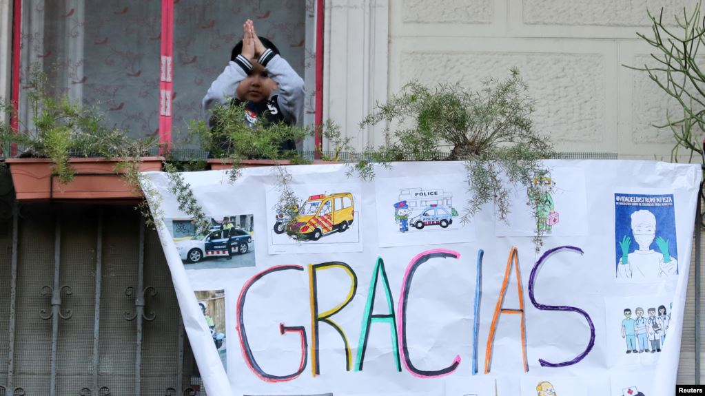 Un niño saluda desde un balcón en Barcelona, España, detrás de un cartel de apoyo a los trabajadores de la salud que luchan contra el coronavirus, el 11 de abril de 2020 / REUTERS