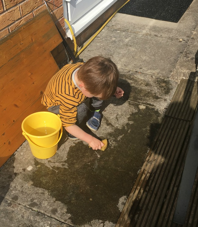 boy-washing-paving-slabs-with-sponge